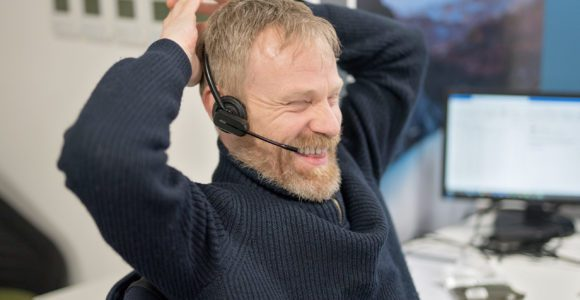 Chris smiles whilst engaging over the phone.
