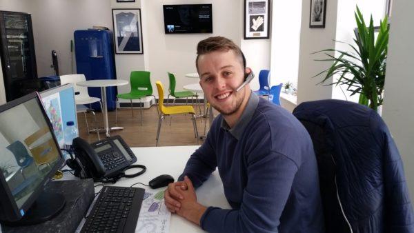 Daniel Philbin at work station, smiles for camera.