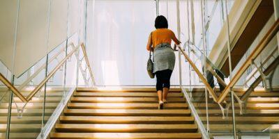 Woman climbing a large set of modern stairs.