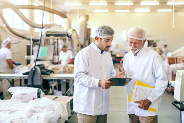 Two men in white lab coats and hair-nets discuss work.