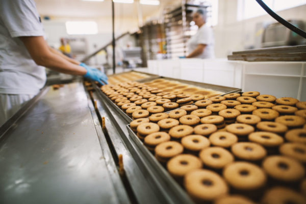 Production of biscuit product, overseen by worker in blue gloves.