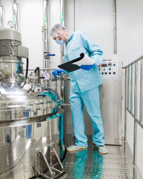 Operations Manager Checking Over Manufacturing Machine